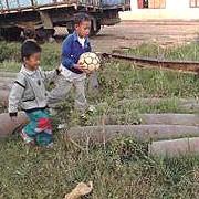 Children playing amongst munitions debris